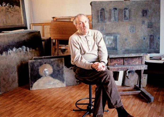Zoran Music sitzend vor einem Gemälde